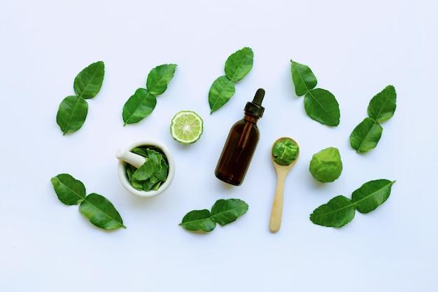 Bouteille d'huiles essentielles et de fruits de bergamot fesh avec feuilles isolé sur blanc