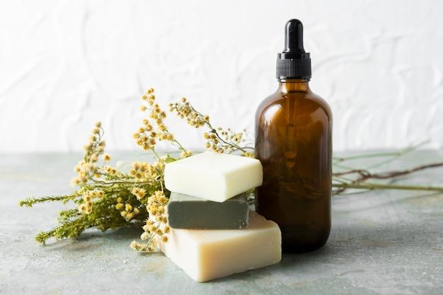Bouteille d'huiles de soin à côté de différents savons