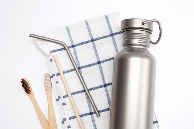 Bouteille d'hydratation et pailles réutilisables en acier inoxydable avec brosses à dents en bambou. concept zéro déchet.