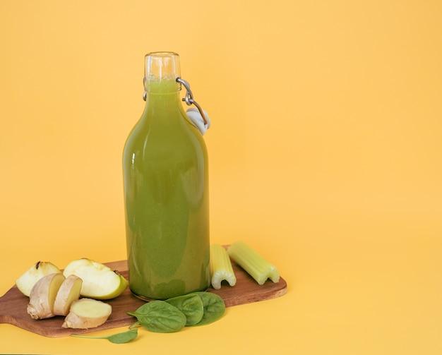 Bouteille de jus d'épinards et planche de cuisson avec légumes et fruits. copiez l'espace.
