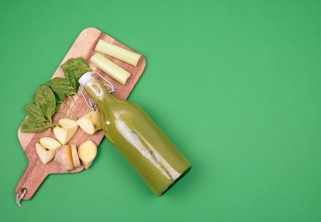 Bouteille de jus d'épinards et planche de cuisson avec légumes et fruits