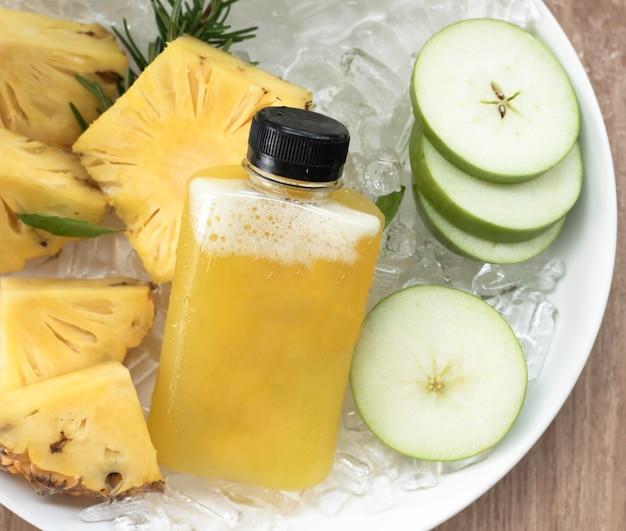 Bouteille de jus de fruits frais beaucoup de gouttes d'eau, ananas en tranches et pomme verte floue