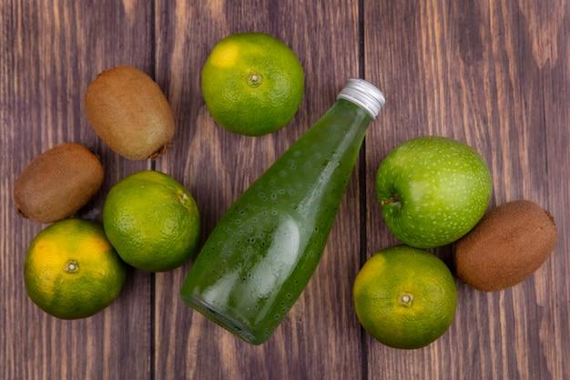 Bouteille de jus de vue de dessus avec kiwi mandarines et pomme sur mur en bois