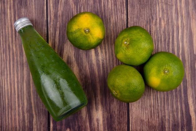 Bouteille de jus de vue de dessus avec des mandarines vertes sur le mur en bois