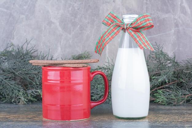 Une bouteille de lait avec arc et verre sur marbre