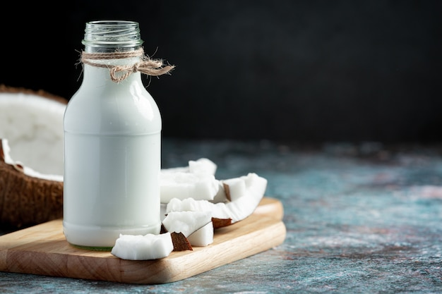 Bouteille de lait de coco mis sur une planche à découper en bois