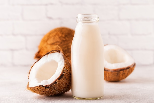 Une bouteille de lait de coco et de noix de coco sur fond clair.