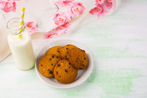 Bouteille de lait avec paille et biscuits