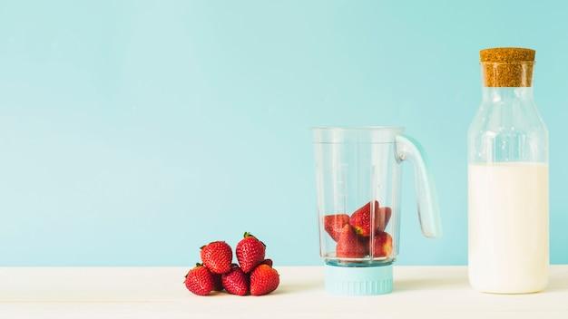 Bouteille de lait près de fraise dans un mélangeur sur une table en bois