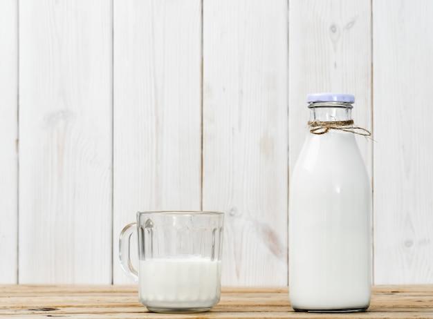 Bouteille de lait et verre à moitié plein avec du lait sur une table vintage en bois