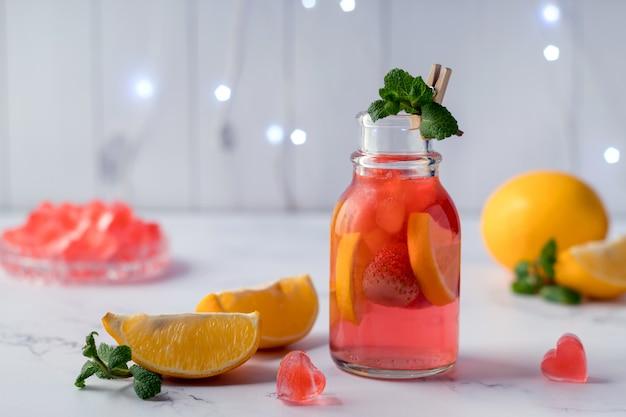 Bouteille avec de la limonade aux fraises rafraîchissante et des glaçons en forme de coeur sur une table en marbre. boisson saint valentin
