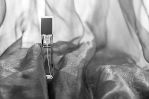 Bouteille de liquide allongée sur tissu avec des vagues teintées de ton sépia