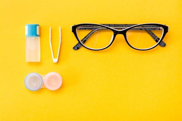 Une bouteille de liquide, un récipient et des pincettes, des lunettes sur un fond jaune