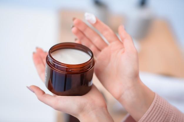 Une bouteille à la main. produit de soin capillaire.
