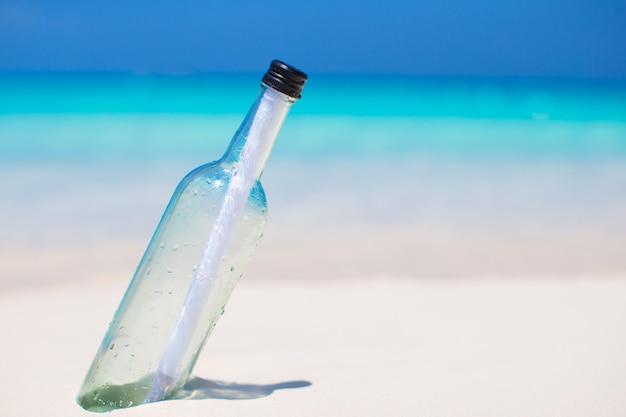 Bouteille avec un message enfoui dans le sable blanc