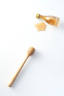 Bouteille de miel en bois et petite bouteille de miel sur blanc