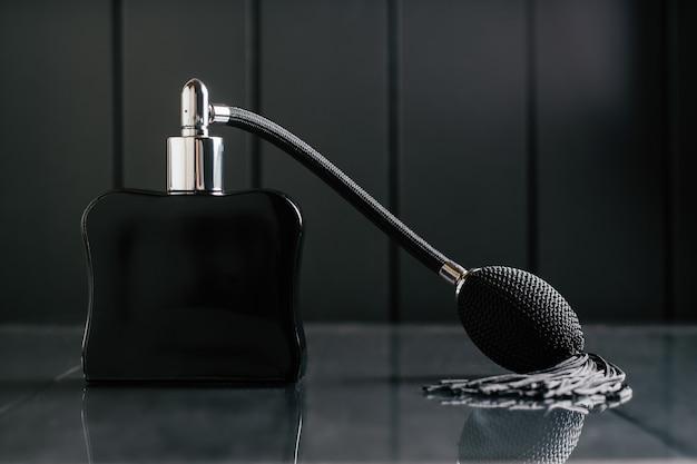 Une bouteille noire d'eau de toilette ou de parfum avec une longue pompe à pompon se dresse sur un fond sombre sur une surface réfléchissante. espace de copie