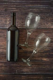 Bouteille noire de vin et de verres sur la table en bois. vue de dessus.