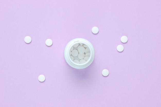 Bouteille ouverte avec des pilules blanches sur une surface violette