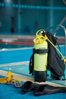 Une bouteille d'oxygène au bord de la piscine, du matériel de plongée