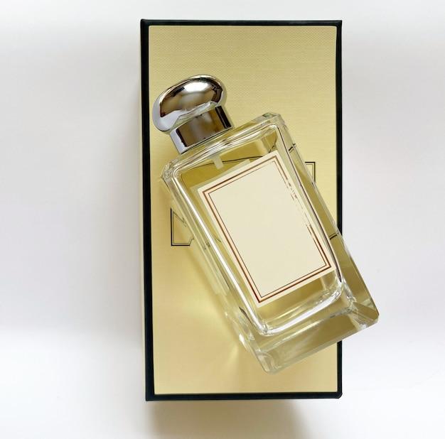 Une bouteille de parfum d'une boîte jaune sur fond blanc isolé