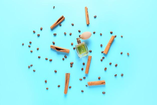 Bouteille de parfum avec de la cannelle et des grains de café sur fond de couleur