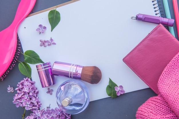 Bouteille de parfum de cercle, portefeuille, brosse à cheveux et pinceau de maquillage avec différentes fleurs, liste blanche horizontale avec place pour le texte
