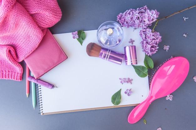Bouteille de parfum de cercle, portefeuille, brosse à cheveux et pinceau de maquillage avec différentes fleurs