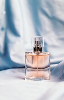 Une bouteille de parfum féminin sur un tissu texturé en soie