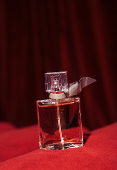 Une bouteille de parfum féminin sur un tissu de velours glamour foncé