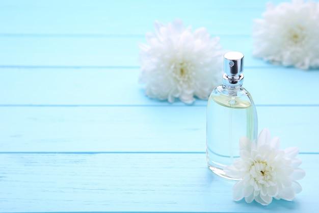 Bouteille de parfum à fleurs blanches sur bleu