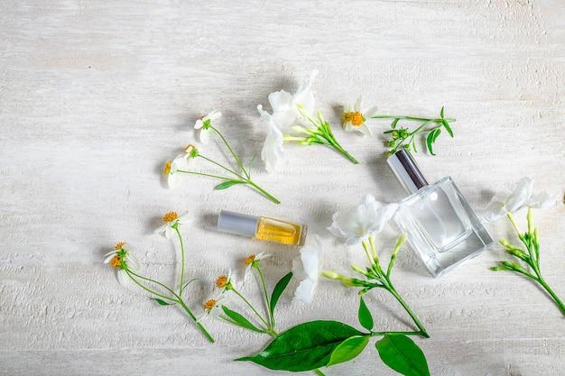Bouteille de parfum avec des fleurs sur fond blanc