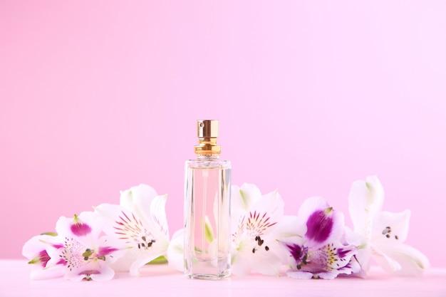 Bouteille de parfum avec des fleurs rose