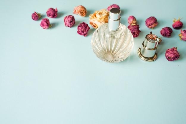 Bouteille de parfum de fleurs roses sur fond bleu pastel