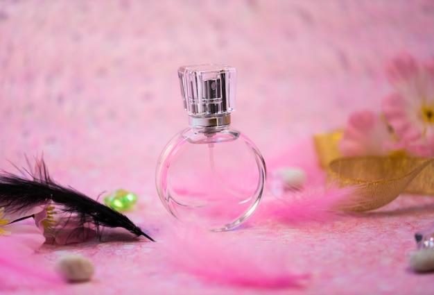 Bouteille de parfum sur fond rose