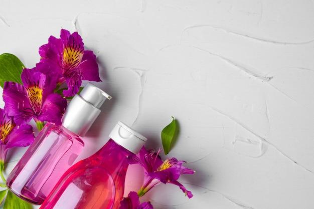 Bouteille de parfum ou d'huile aromatique dans un bouquet de fleurs fraîches