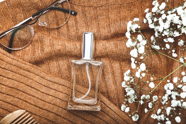 Bouteille de parfum avec des lunettes sur pull tricoté
