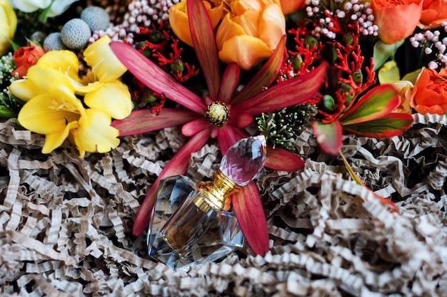 Bouteille de parfum de luxe avec des fleurs dans la boîte-cadeau. parfumerie, cosmétique, collection de parfums. vue de dessus