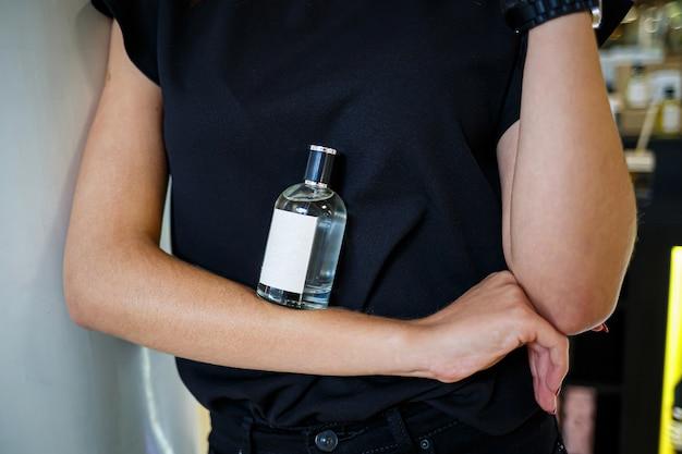 Bouteille de parfum main féminine. jeune femme tenant une bouteille de parfum. parfums à la mode dans les mains des femmes. la fille vaporise du parfum. de belles mains de femmes.