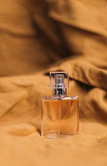 Une bouteille de parfum parfumé pour femmes sur un tissu texturé marron