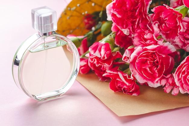 Une bouteille de parfum de personne et un bouquet de fleurs sur une surface rose. donnez des cadeaux et des fleurs à la personne. recevoir des cadeaux de personnes aimées en vacances