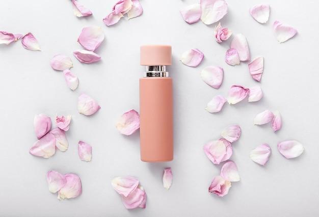 Bouteille de parfum avec des pétales de fleurs de rose sur fond blanc