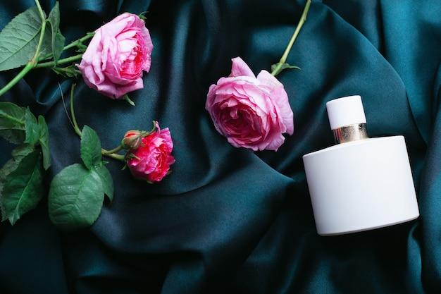 Bouteille de parfum avec des roses sur un fond de tissu vert