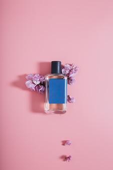 Bouteille de parfums sur mur rose avec des fleurs