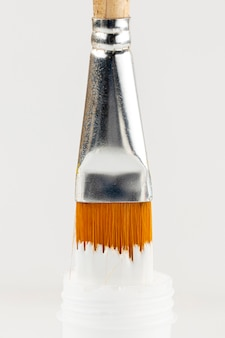 Bouteille de peinture blanche et pinceau trempé