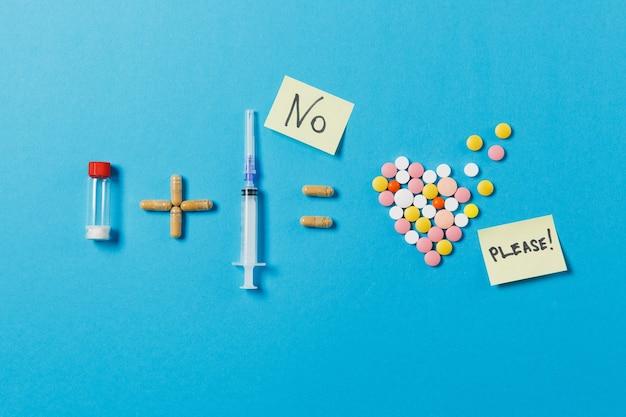 Bouteille de pilules et aiguille de seringue équivaut à des comprimés ronds colorés en forme de coeur isolé sur fond bleu