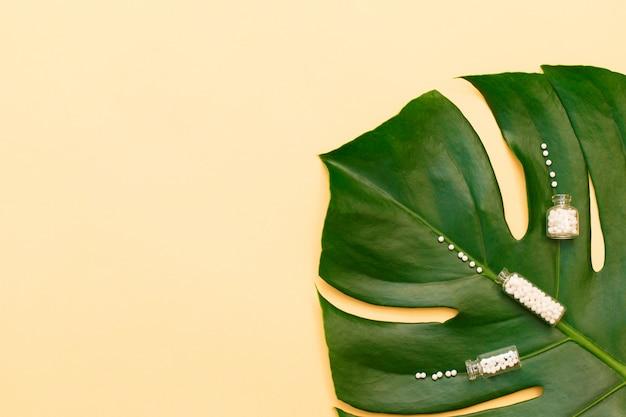 Bouteille avec des pilules homéopathiques sur feuille de palmier et fond beige