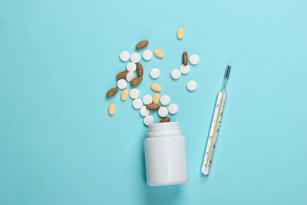 Bouteille de pilules avec thermomètre sur fond bleu