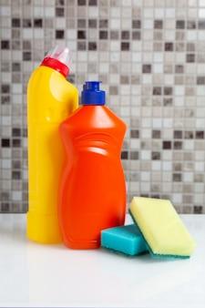 Bouteille en plastique avec agent nettoyant et éponges sur la table