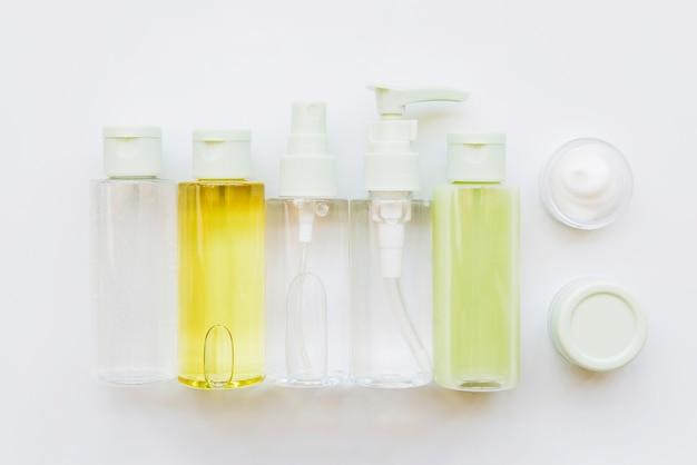 Bouteille en plastique cosmétique avec différents bouchons et crème hydratante sur fond blanc